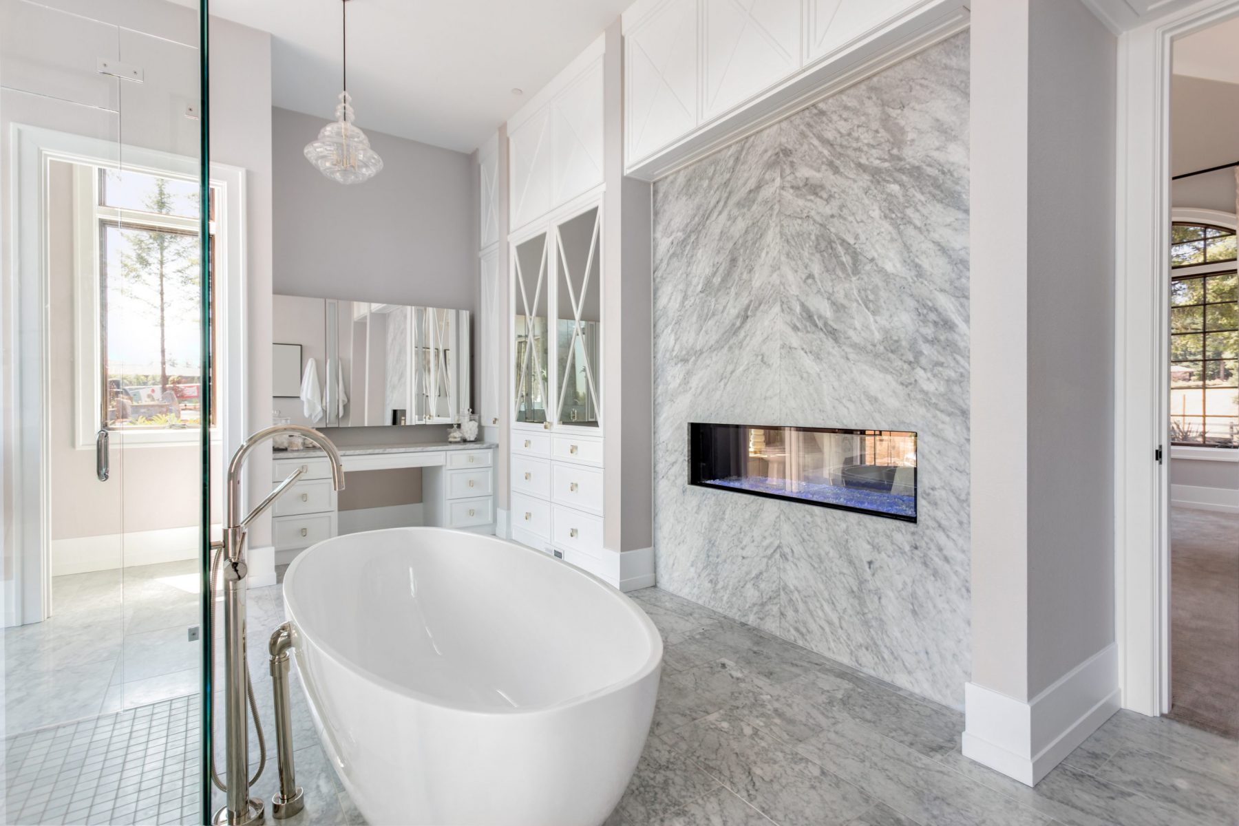 Luxurious Master Bathroom in New Home with Fireplace and Large Bathtub