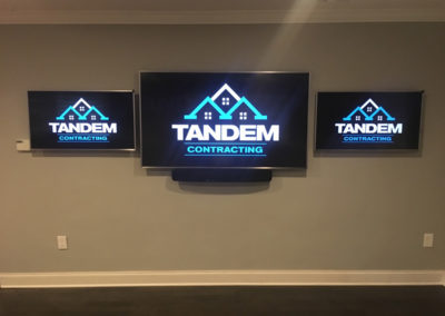 three televisions with Tandem Contracting Logo