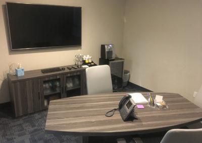 tandem office space with desk chairs television and mini fridge