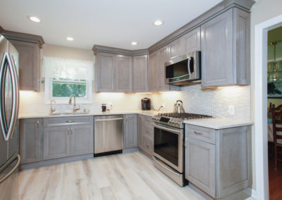 The team of professional contractors at Tandem Contracting completed this kitchen renovation. This kitchen features stainless steel appliances, new countertops, new cabinets, and an updated wood floor.
